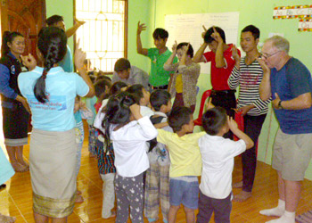 Preschool children and adults learn Lao sign language.