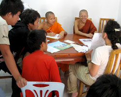 Lao students and novice monks practice English with a visitor in Luang Prabang, Laos.