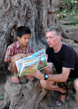 Sasha reads to a boy sitting on a tamarind tree.